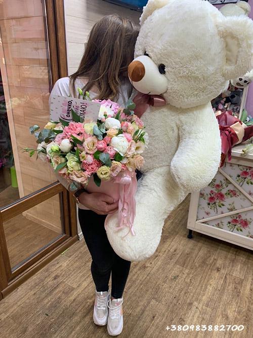 Большой плюшевый медведь и букет цветов